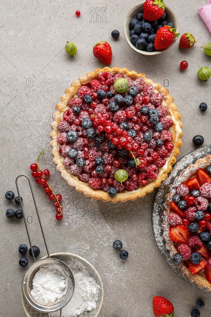 Top view of two freshly made berry tarts sprinkled with powdered sugar