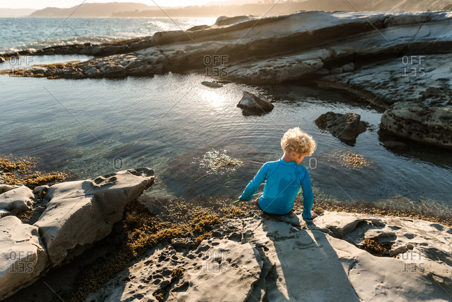 Rear view of young boy playing in tide pools on coast