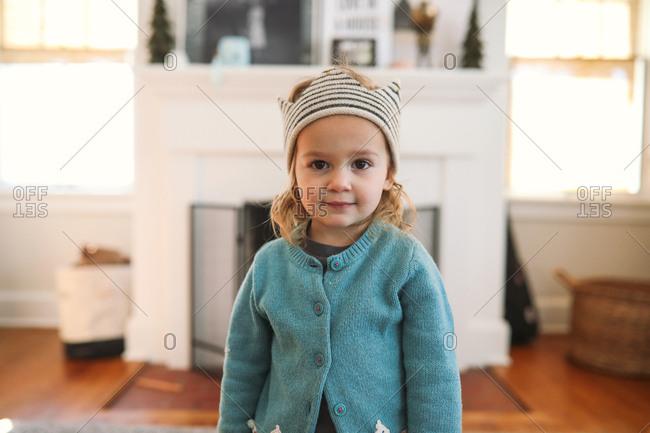 Adorable toddler girl wearing striped hat