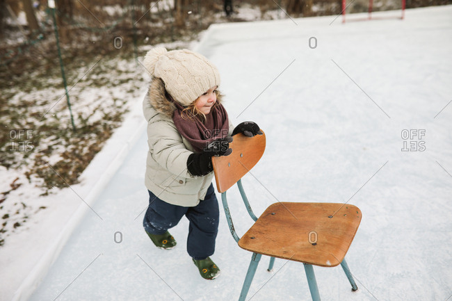 Toddler girl pushing chair on ice in winter