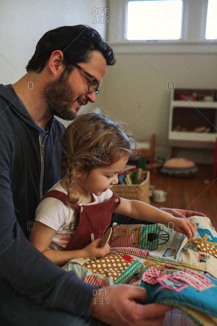 Dad reading fabric book to toddler daughter