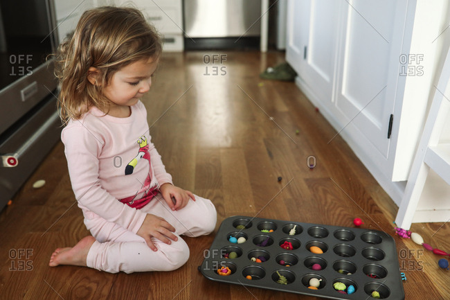 Toddler girl playing with toys and muffin pan on floor