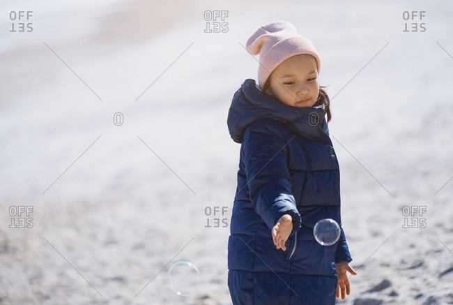 Cute girl playing soap bubbles at the beach