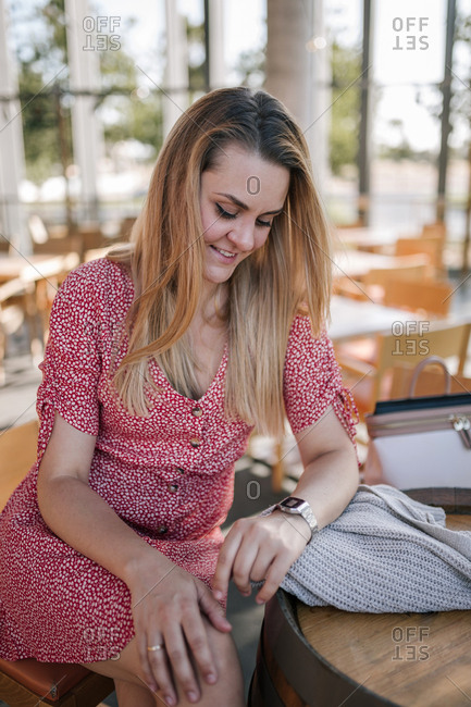 Blond woman checking her watch and waiting in a coffee shop