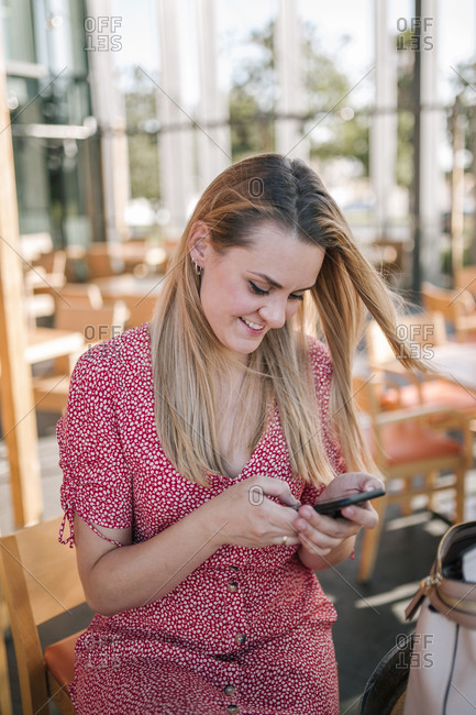 Blonde woman typing on her mobile phone while waiting in a coffee shop