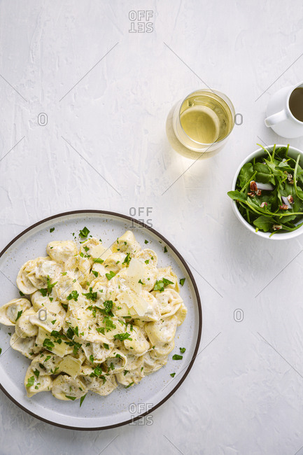 Plate of tortellini served with a side salad