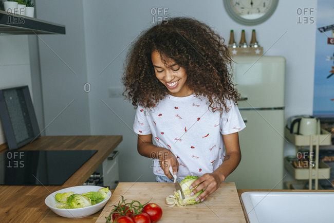 Woman cutting lettuce for salad in the kitchen