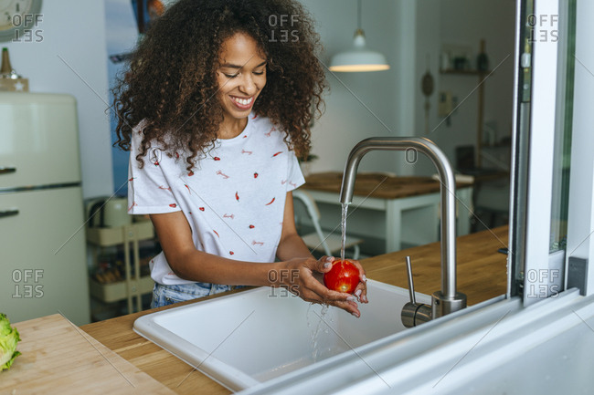 Woman washing tomato in the kitchen