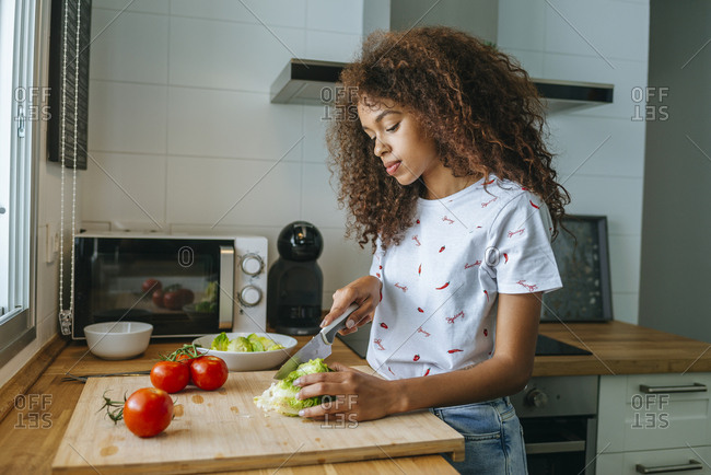 Woman in the kitchen cutting lettuce for salad