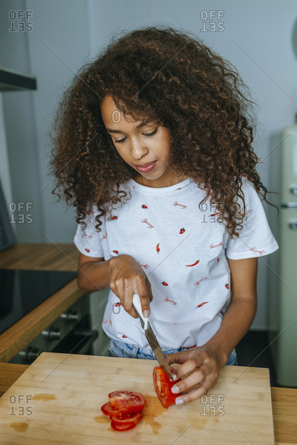 Woman in the kitchen cutting tomato on cutting board