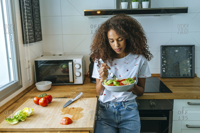 Woman with lettuce and tomato salad in the kitchen