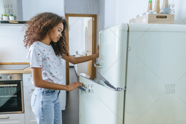Woman opening the fridge in her home