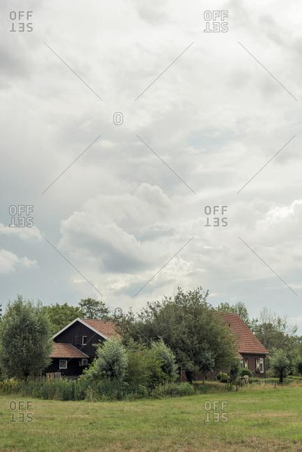 A brown farmhouse under cloudy skies