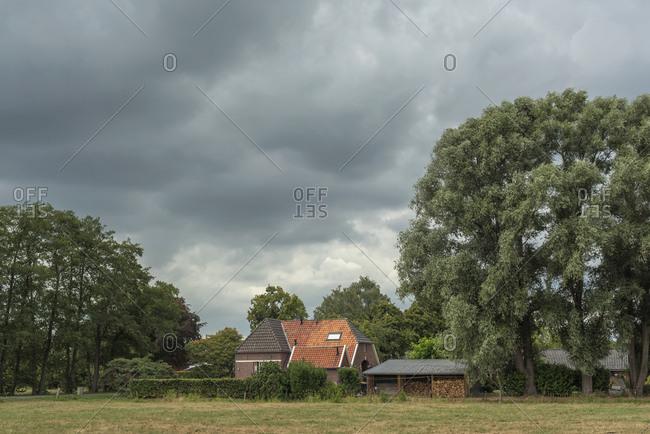 A brick farmhouse under dark cloudy skies