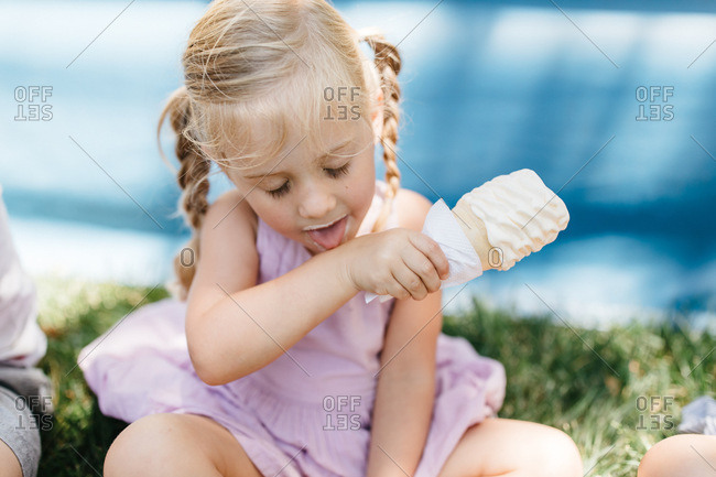 Little girl licking ice cream from her arm at the Alameda County Fair, California