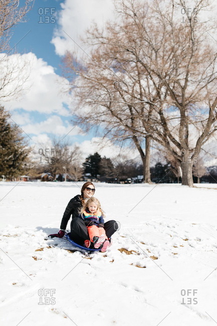 Mother sledding with daughter on snowy hill