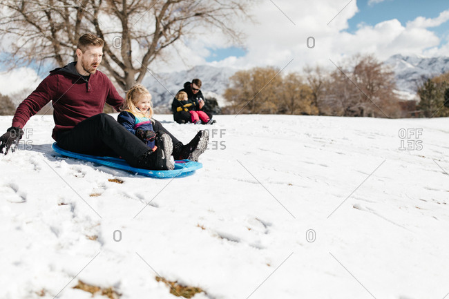 Father sledding with daughter on snowy hill