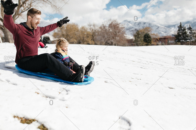 Father and daughter sledding on snowy hill
