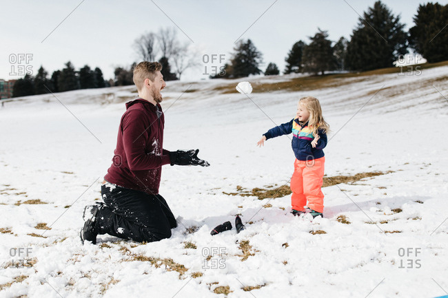 Father and daughter throwing snowballs at each other