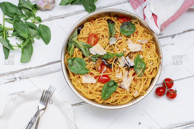 Pasta with aubergines, tomato sauce and fresh basil served with parmesan