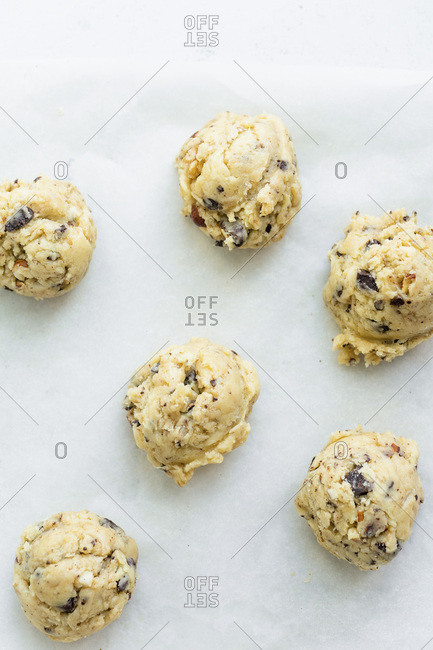 Uncooked butter for chocolate chip cookies put with an ice-cream scoop on parchment paper