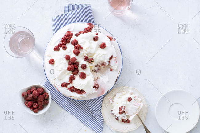 Pavlova meringue cake with whipped cream and fresh raspberries. Seasonal summer dessert