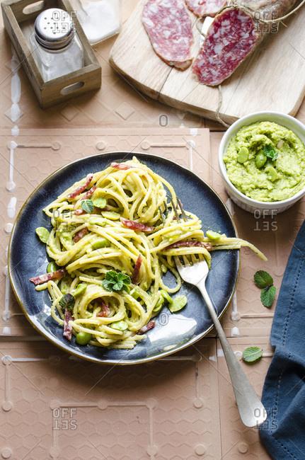 Spaghetti with favabean pesto and salami