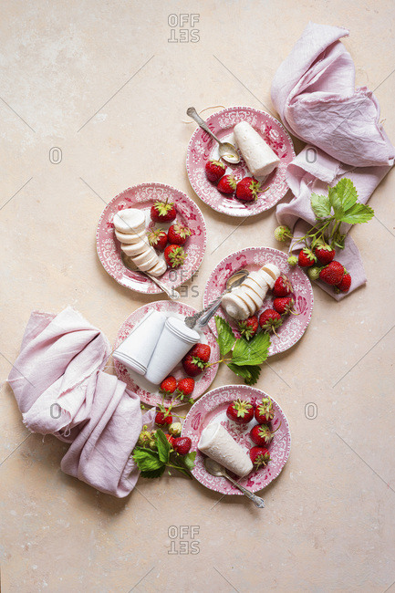 Strawberry Kulfi served on pink china plates , pink linen with fresh picked strawberries.