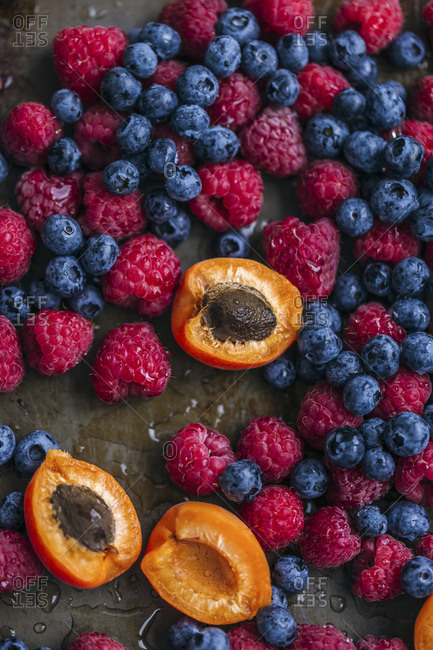 Fresh raspberries, blueberries and apricots on a rustic metal surface