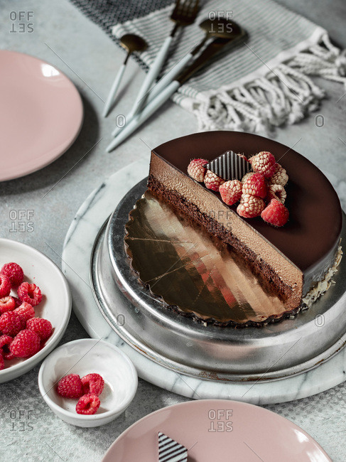 Chocolate truffle cake with raspberries and chocolate decoration on top.