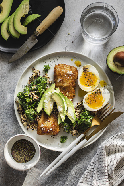 Baked fish with quinoa, kale and avocado with soft boiled eggs on the side served on white plate