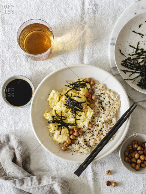 Japanese style scrambled eggs with rice chickpeas and nori served in white bowl with chopsticks
