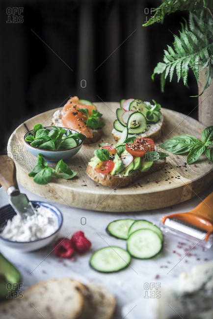 Bruschetta on a bread board, along with various vegetables.