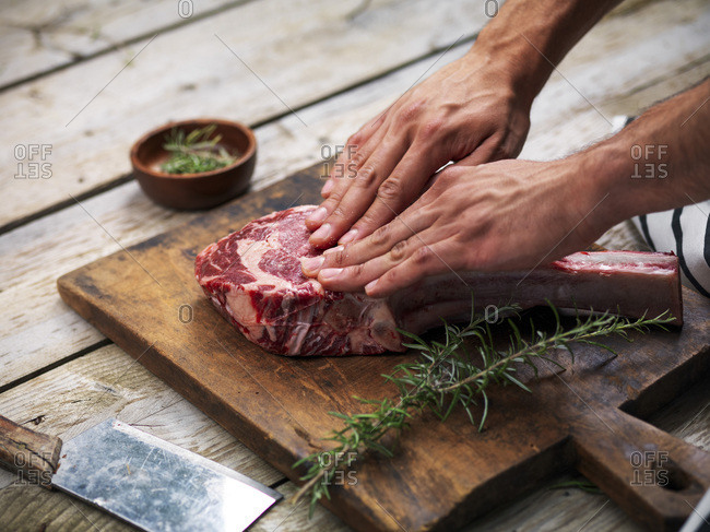 Hands curing a raw fresh angus meat tomahawk on a wooden cutting board with rosemary, salt and butcher's knife