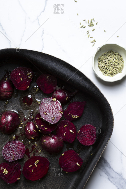 Beetroot pieces in a roasting pan, with olive oil and sprinkled with fennel seeds, ready for the oven. The surface is a marble tile and there is a small bowl of fennel seeds alongside.