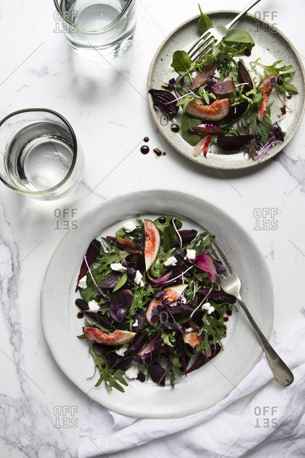 A salad of roasted beetroot, purple carrots and purple onions, with fresh figs, mixed leaves and microherbs, dotted with feta cheese. Two plated servings are on a marble tile surface with glasses of water.