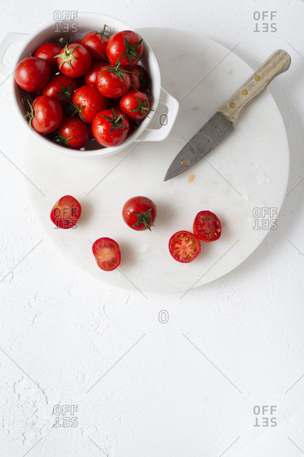 Freshly washed cherry tomatoes in a white colander, prepared for slicing. Overhead view