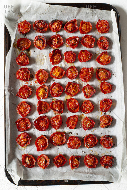 Oven roasted cherry tomatoes, sprinkled with sea salt and cracked black pepper, on an oven tray. Overhead view.