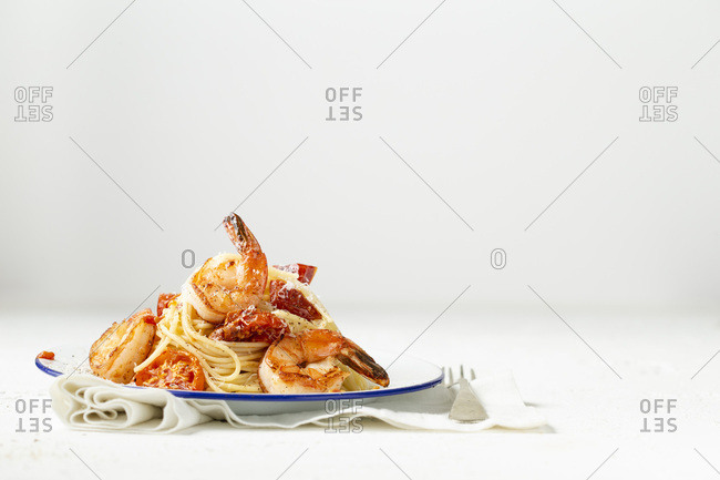 Spaghetti with pan seared prawns, oven roasted tomatoes and parmesan, on an enamel plate with a fork and linen. Light background.