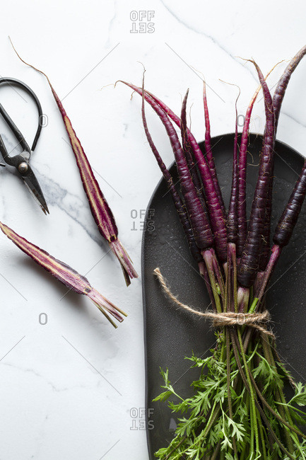 A bunch of washed purple carrots tied with jute twine on an oblong charcoal platter. The surface is a marble tile a halved carrot and a pair of scissors are alongside.