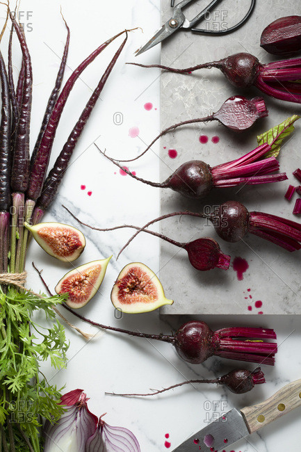 Baby beetroots, purple carrots, purple onions and figs, being sliced and prepared on a marble tile surface. A knife, scissors and a marble board are in the shot.