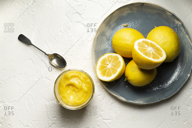 Fresh lemons, whole and sliced in half, arranged on a blue hand made plate. A jar of home made lemon curd and a spoon are alongside.
