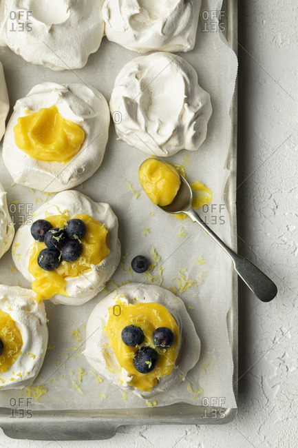 Meringues with lemon curd and blueberries on a baking tray with parchment, on a white textured background. A spoon of lemon curd is on the tray. Lemon zest has been grated over.