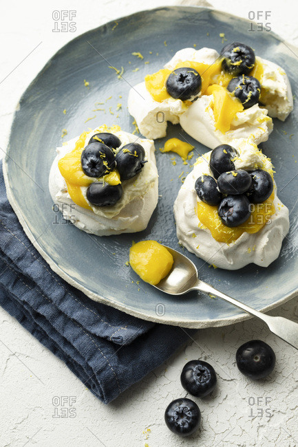 Meringues with lemon curd and blueberries on a hand-made plate, resting on a blue linen napkin. They are garnished with lemon zest and ready to serve. A spoon of lemon curd is on the side.