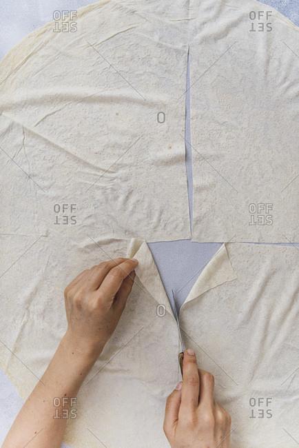 Woman cutting phyllo sheets to make Turkish sigara borek