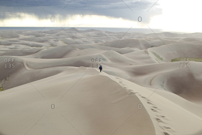 A man walking in atop the Great Sand Dunes in Southern Colorado, USA.