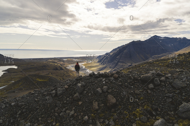A hiker stands near the edge of a cliff at the base of Joklasel Glacier, overlooking the valley towards the Southern Region of Iceland.