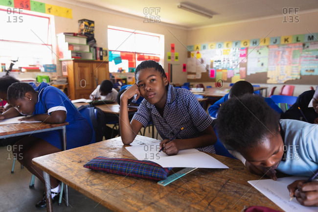 Front view of a young African schoolgirl leaning on her desk and looking up while writing in her notebook during a lesson in a township elementary school classroom, beside her and in the background her classmates are writing in their books