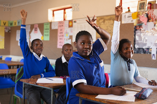 Front view close up of a group of young African schoolchildren sitting at their desks, raising hands to answer a question during a lesson in a township elementary school classroom