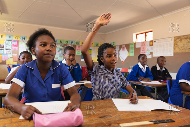 Young African elementary school students sitting at desks with one girl one raising her hand to answer a question during a lesson in a township elementary school classroom in Cape Town, South Africa